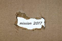 La mission 2017 de mot apparaissant derrière le papier déchiré Photographie stock