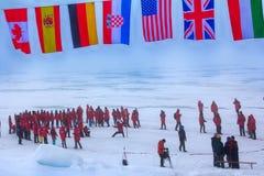 La missione è più: le bandiere di tutti i paesi partecipanti tremano al polo nord Guardie della parte posteriore contro gli orsi  Immagine Stock