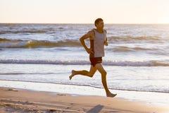 La misura atletica ed il forte corridore equipaggiano l'addestramento sulla spiaggia del tramonto dell'estate nel funzionamento d immagini stock libere da diritti