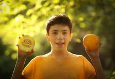 La mitad de la consumición del muchacho del adolescente cortó el melón maduro con la cuchara Fotografía de archivo