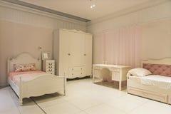La mobilia dei bambini moderni in una camera da letto spaziosa Immagine Stock