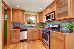 La mobilia della cucina e la parte posteriore marrone chiaro delle mattonelle del mattone spruzzano la disposizione immagine stock