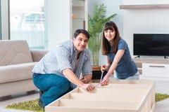 La mobilia di montaggio della giovane famiglia alla nuova casa Fotografie Stock