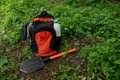 La mochila negra roja con ropa y una pala que se coloca en la tierra con la hierba verde Fotografía de archivo