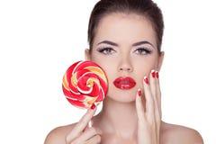 La moda compone. Retrato de la muchacha de la belleza que sostiene la piruleta colorida. Fotografía de archivo libre de regalías