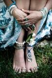 La moda de Boho detalla las manos de la mujer y los pies desnudos en hierba con la porción imágenes de archivo libres de regalías