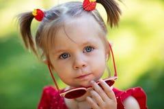La moda embroma a la muchacha en gafas de sol niño adorable del niño en las gafas de sol del espejo, vestidas en un vestido rojo imágenes de archivo libres de regalías