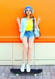 La moda es la muchacha bastante que fresca escucha la música con un monopatín sobre naranja colorida Imagen de archivo