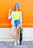La moda que es la mujer bonita escucha la música con un monopatín sobre naranja colorida Imagenes de archivo
