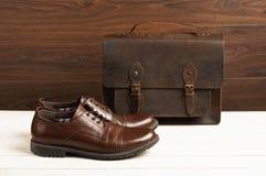 La mode du ` s d'hommes avec les chaussures en cuir brunes et les affaires mettent en sac sur un fond en bois Mode du ` s d'homme Images stock