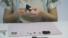 La modista de la muchacha cose Swarovski cristalino a sentido en blanco para la broche metrajes