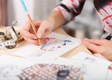 La modista está dibujando un bosquejo de la moda Foto de archivo libre de regalías