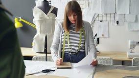 La modista profesional está haciendo notas en libreta y está mirando bosquejo de la ropa mientras que trabaja en la tabla del est almacen de metraje de vídeo