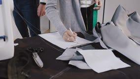 La modista profesional joven que toma las medidas para el traje de costura en los sastres hace compras La costurera con la cinta  almacen de video