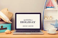 La mofa del ordenador portátil encima de la plantilla con los artículos de la playa y la decoración casera se opone Vacaciones de foto de archivo libre de regalías