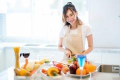 La moglie asiatica prepara l'insalata e gli spaghetti per la cena parrty fotografia stock