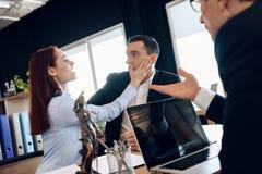 La moglie cattiva schiaffeggia il fronte sorpreso del marito, sedentesi alla tavola del ` s dell'avvocato per dissolvere il matri immagine stock libera da diritti