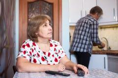 La moglie caucasica guarda la TV ed i resti, marito aiuta nella cucina - piatti dei lavaggi Fotografie Stock Libere da Diritti