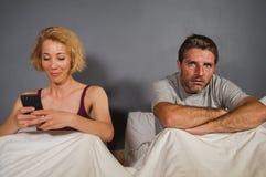 La moglie che per mezzo del telefono cellulare a letto con il suo marito frustrato arrabbiato e la sensibilità dell'uomo ha trasc immagine stock