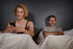 La moglie che per mezzo del telefono cellulare a letto con il suo marito frustrato arrabbiato e la sensibilità dell'uomo ha trasc immagini stock libere da diritti