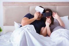 La moglie ed il marito con gli occhiali di protezione di realtà virtuale nel letto fotografie stock libere da diritti
