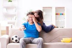 La moglie infelice che il marito sta guardando il calcio fotografia stock