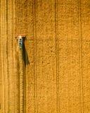 La moissonneuse fonctionnant dans le domaine et fauche le bl? l'ukraine Silhouette d'homme se recroquevillant d'affaires photographie stock