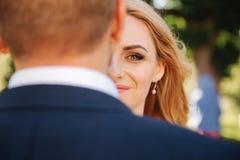La moitié de jeunes mariées du visage est cachée derrière le dos du marié photos libres de droits