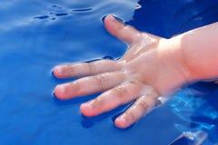 La moitié de main d'enfant a plongé dans l'eau de la piscine en plastique bleue images stock