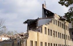 La moitié s'est effondrée maison de brique couverte en poussière et débris Images stock