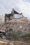 La moitié s'est effondrée maison de brique couverte en poussière et débris Image stock