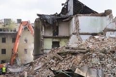La moitié s'est effondrée maison de brique couverte en poussière et débris de machine de coup retentissant Image libre de droits