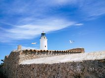 La Mola Lighthouse with blue sky and flying seagulls stock images