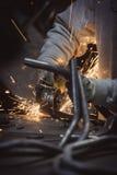 La molatura dei cicli del tubo d'acciaio con molti scintilla su una tavola di lavoro Immagini Stock