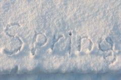 La molla di parola è scritta nella neve illuminata dal sole Fotografia Stock Libera da Diritti