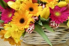 La molla multicolore del mazzo fiorisce con il canestro di vimini su di legno Immagine Stock