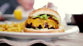 La momia alimenta a niño una hamburguesa sabrosa, cheeseburger almacen de metraje de vídeo