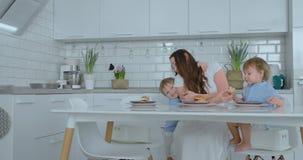 La momia con dos hijos jovenes está comiendo las hamburguesas en casa metrajes