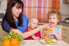 La momia feliz hermosa con los niños come la fruta Foto de archivo