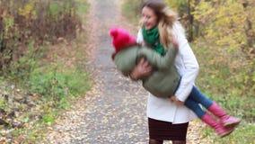 La momia feliz y la hija de la familia que caminan en otoño parquean almacen de video