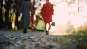 La momia feliz y la hija con los panieres coloridos que caminan con otoño parquean en fondo borroso del bokeh 1920x1080 almacen de metraje de vídeo