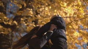 La momia se sostiene en las manos de su hijo en el parque del otoño metrajes