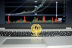La moneda de oro del bitcoin en un teclado de plata del ordenador portátil y el diagrama trazan el gráfico en una pantalla como f fotos de archivo