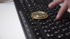 La moneda de oro del bitcoin gira en el teclado metrajes