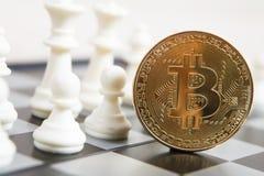 La moneda de oro del bitcoin simboliza elementos con el tablero de ajedrez foto de archivo