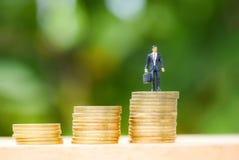 La moneda de oro intensifica el crecimiento del éxito empresarial del hombre de la pila del dinero de la moneda de la escalera de foto de archivo