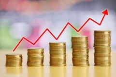La moneda de oro de la pila del concepto crecido financiero y las flechas rojas son ri foto de archivo