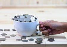 La moneda en una taza del café con leche descansa sobre una tabla y un aroun de madera fotografía de archivo