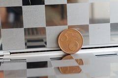 La moneda euro con una denominación de 5 centavos euro en espejo refleja la cartera, fondo a cuadros Imágenes de archivo libres de regalías