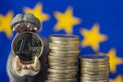 La moneda euro en la boca de la estatuilla del hipopótamo, UE señala por medio de una bandera Imagen de archivo libre de regalías